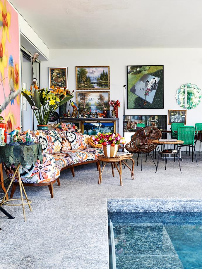 Pool room chic Rattan furniture from the '50s offers another place to sit, chat and relax, while vases of blooms add flourishes of colour. The rabbit artwork on the wall is called Rabbit and Radishes by Italian artist Graziella Marchi.