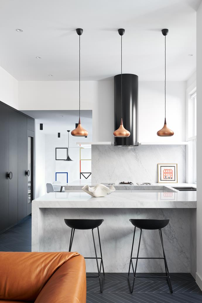 Brass pendants from cult hang from the ceiling in this kitchen which combines traditional elements with modern styling.