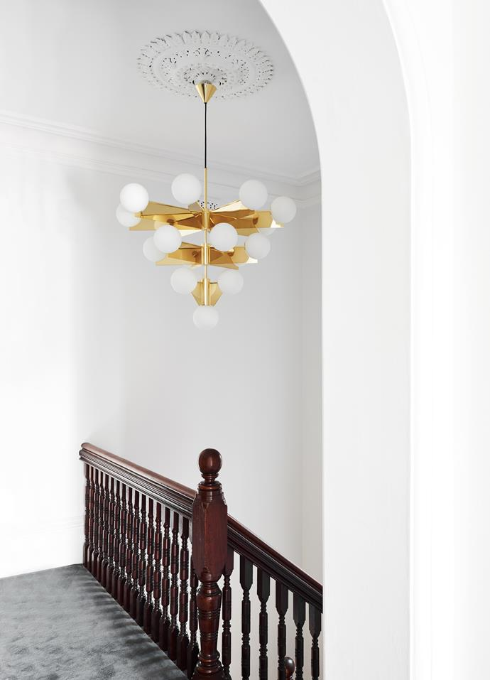 A gold, Dixon chandelier hangs above the staircase, demonstrating the home's expert fushion of classic meets modern.