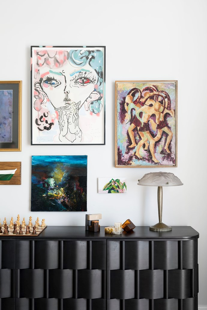 A bespoke black cabinet is positioned beneath the owners' prized art collection