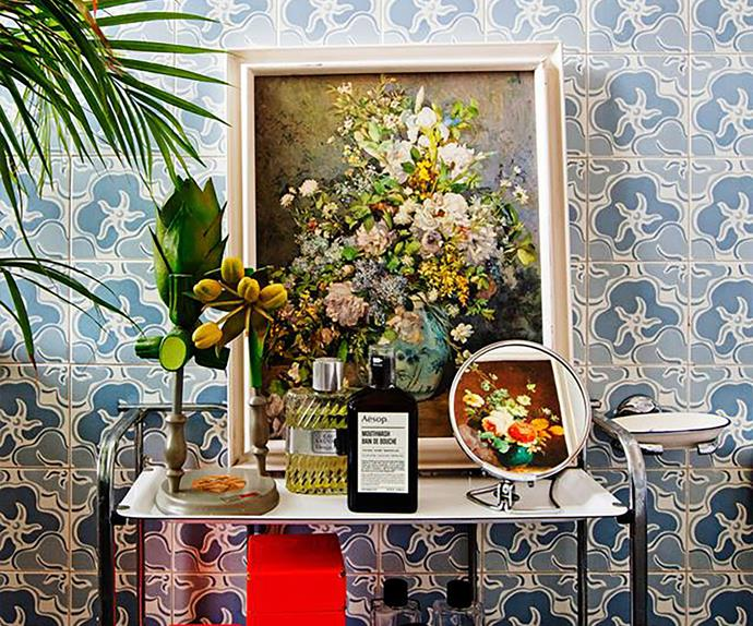 Mirror, artwork and trinkets on top of a bathroom trolley