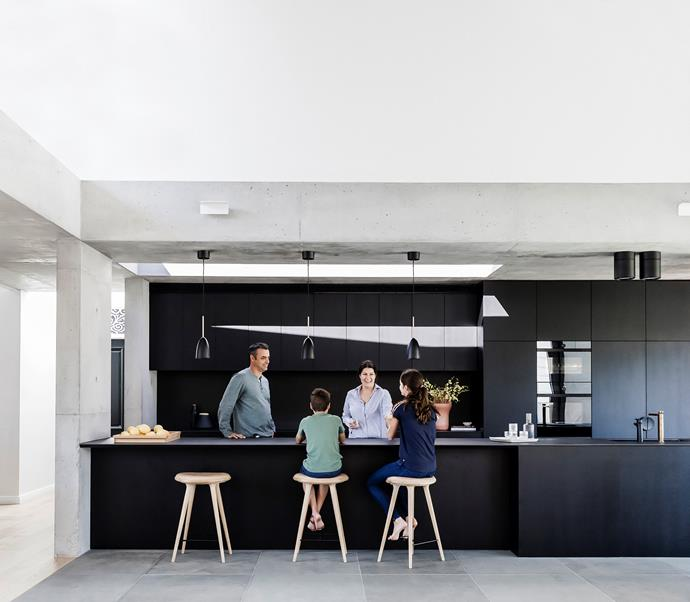 The all-black kitchen packs a punch, contrasting against the concrete surfaces.