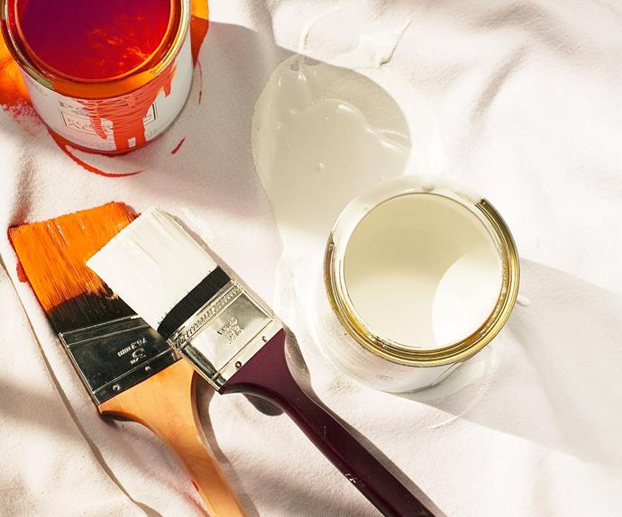 Paint brushes with open tins of paint