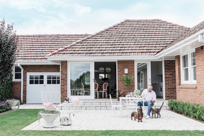 """Owner Stewart Horton with dachshund Mortimer (a house warming present to partner Brian) and Russian blue feline Lucinda. Carrara marble paving defines the north-facing entertaining area and ties in with terrazzo elements inside. """"The steps are a nice place to sit and enjoy a cup of coffee in the winter sun,"""" says Stewart."""