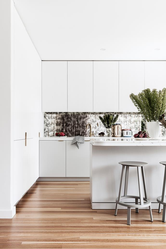 """Stewart demolished a wall to create a generous kitchen with concealed pantry. """"It's opened up the house so much,"""" he says. Antiqued mirror panels line the splash-back."""