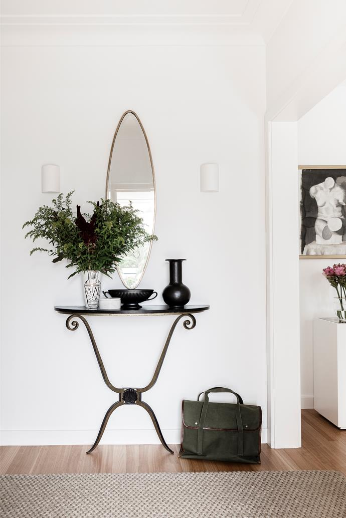 A handsome French console welcomes guests towards the wide entrance to the open-plan living and dining room.