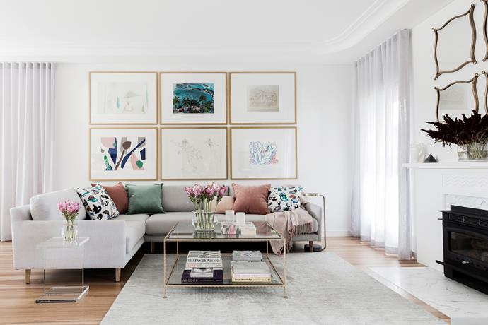 Identical frames in this living room turn diverse works of art into a cohesive collection.
