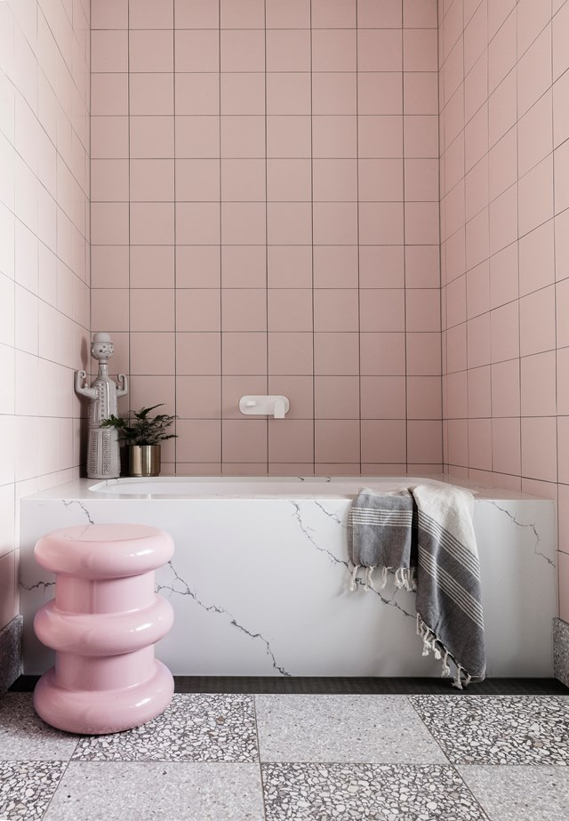 This retro-style bathroom features square pink tiles, a striking marble bath tub and a bubblegum pink stool. *Photo:* Maree Homer / *bauersyndication.com.au*