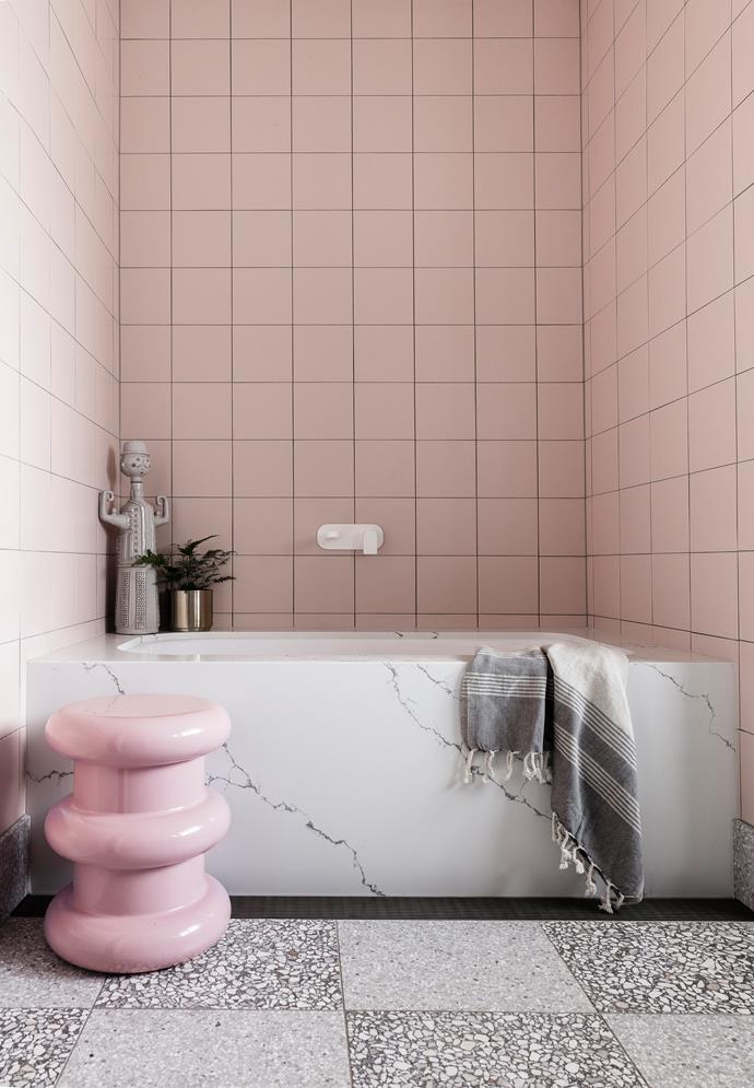 The pink bathroom features grey Fibonacci stone floor tiles and a marble bath tub.