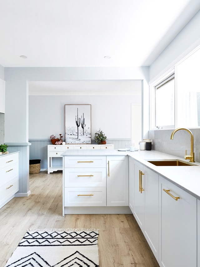 "Brass cupboard handles paired with a gold-toned sink and tapware create a cohesive look while adding a luxe touch to this [classic Shaker-style kitchen](https://www.homestolove.com.au/3-clever-kitchen-renovation-makeovers-6665|target=""_blank"")."