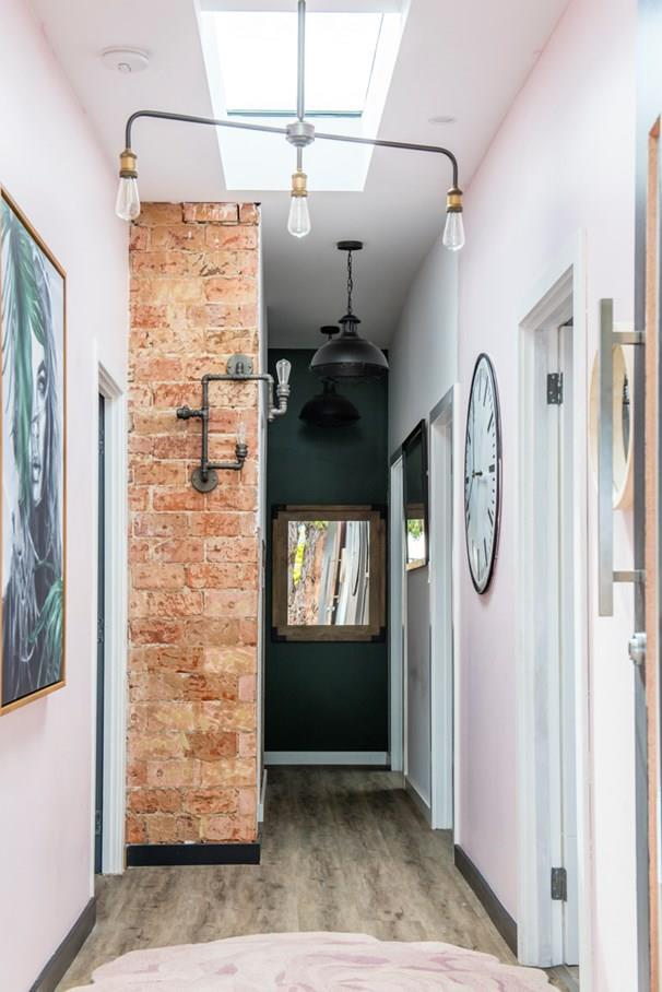 Four different wall finishes were used in the hallway. Pink, white and green paint, and exposed brick. *Photo: 7Plus*