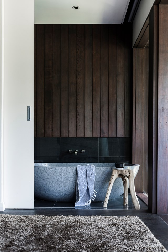 """An 'Apaiser' stone bath becomes the centre of relaxation in this spa like timber bathroom in a [broken-plan family home in Sydney](https://www.homestolove.com.au/broken-plan-concept-for-restored-1920s-family-home-6671