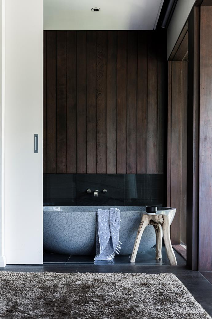 A timber stool counters the sleek Apaiser stone bath.