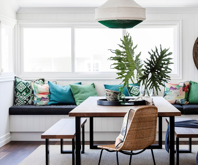 Coastal style dining room with bench seating and green throw cushions