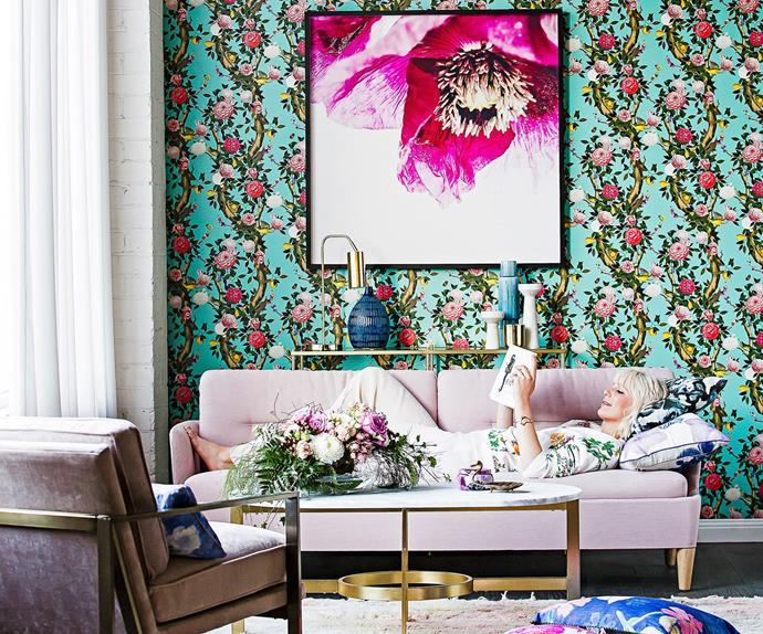 Woman reclines on a powder pink lounge in a room with bright floral and turquoise wallpaper