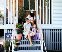 Patience Hodgson with her husband John Patterson and two kids on their home's front steps.