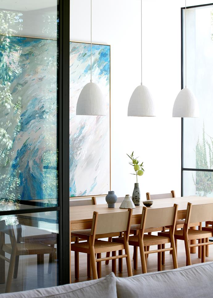 An artwork by Tat Georgieva presides over the 'Huxley' dining table and chairs from Jardan. Anna Charlesworth pendant lights.