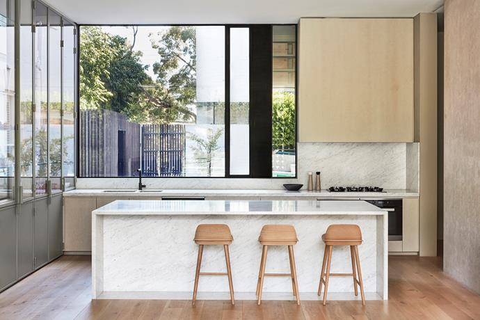 In the kitchen, a custom joinery unit has been painted sage green, its glass shelving and doors leaving nothing to the imagination. Muuto 'Nerd' bar stools.