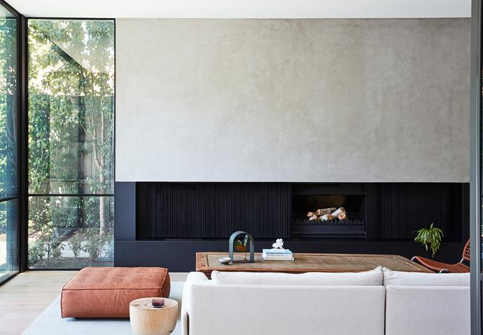 In the living room is a Carlo Colombo for Arflex 'Faubourg' sofa from Poliform, Mark Tuckey 'Egg' side table, and Living Divani leather pouf on a custom silk rug from Artoz. Steel fireplace.
