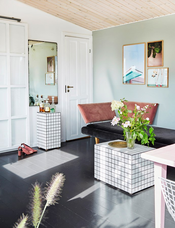 The living room is a peaceful space flooded with natural light. The sofa, coffee table and bar table are from Cecilie and Daniel's company Øje-blik. Posters from Paper Collective pull the look together with hints of pink, mirroring key pieces in the room. The mirror was a flea market find.