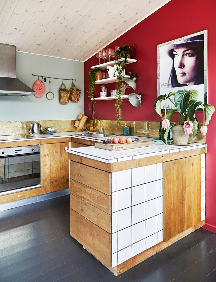 The kitchen was designed and built by the couple themselves, using high-glazed tiles and oak wood. The poster on the wall is the cover of Cecilie's first album.