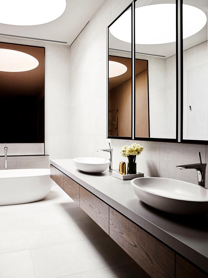 Man-made materials such as reconstituted stone on the bathroom surfaces were used throughout. The monochromatic master bathroom is lit by a generous skylight.