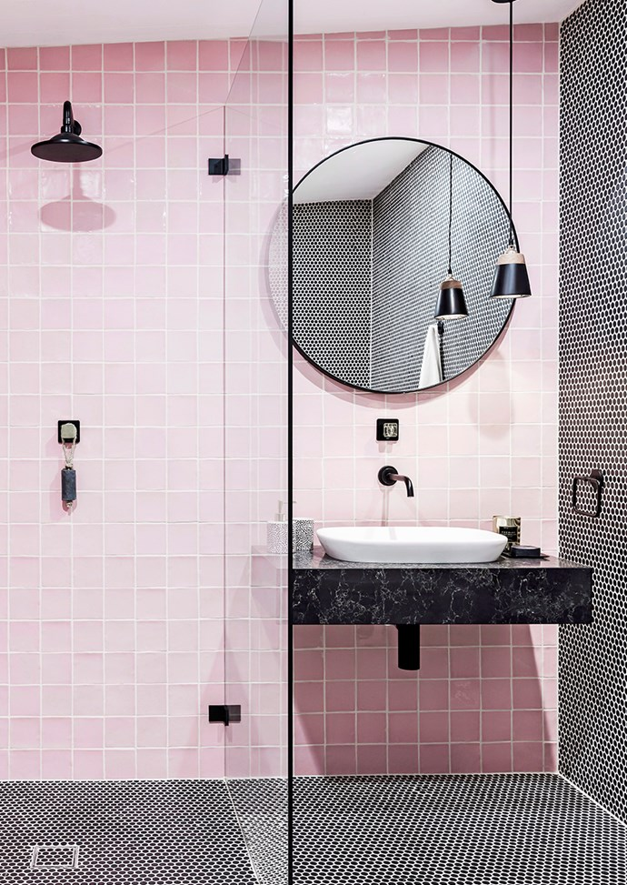 White grout gives bathrooms a Scandi-style edge. Here, black Penny Round tiles and matte black accents allow the bathroom's pink to pop.  *Photo: Maree Homer / Bauersyndication.com.au*