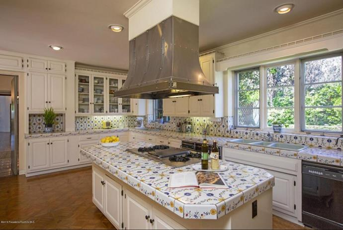 The generously sized kitchen features hand-painted tiles on the splash back and benchtops. *Photo: Compass*