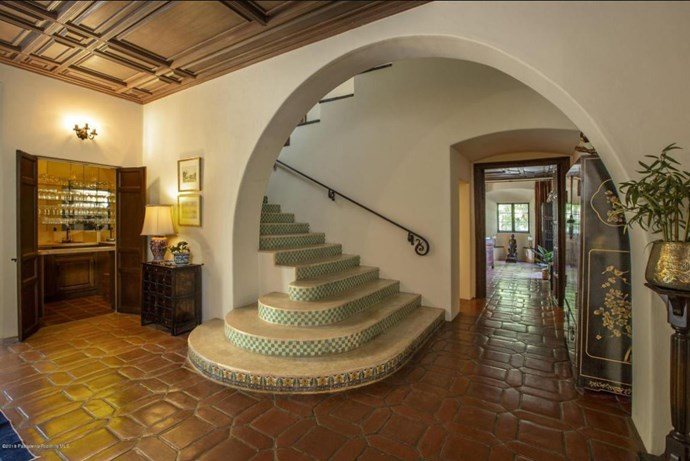 The home features a grand, tiled staircase and walk-in bar. *Photo: Compass*