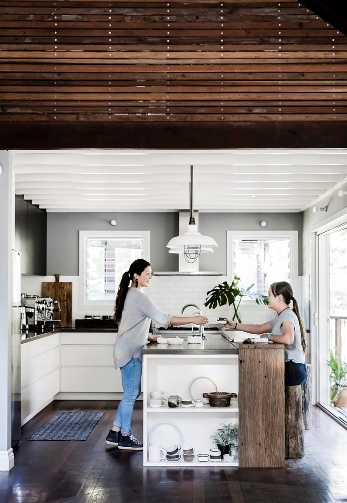"Vrinda and Gopi in the bright and welcoming space Vrinda designed. ""My only disappointment is that I didn't go with a double sink,"" she says. Gavin made the breakfast bar from salvaged wharf timbers, and the stools from an old gum tree."