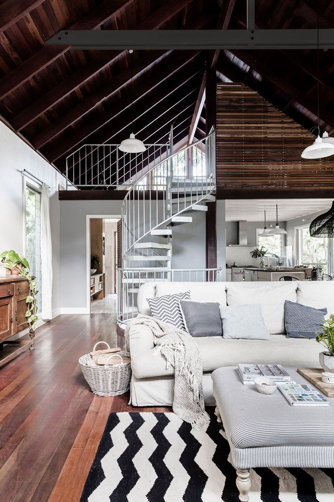 The staircase connects this main level with the main loft bedroom above and children's rooms below. Plush, soft textiles make a comfy counterpoint to durable timber and steel.