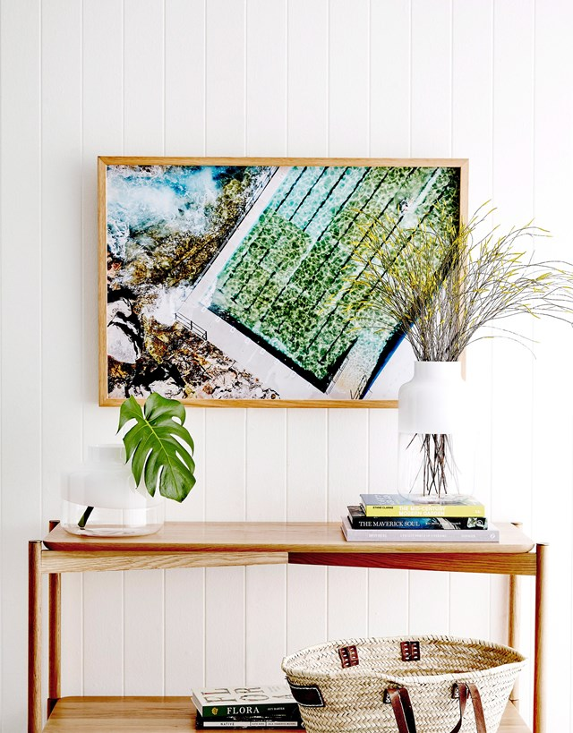 Blues, greens and natural tones in this artwork are complemented by timber furniture pieces and fresh greenery. *Photo:* Will Horner / bauersyndication.com.au