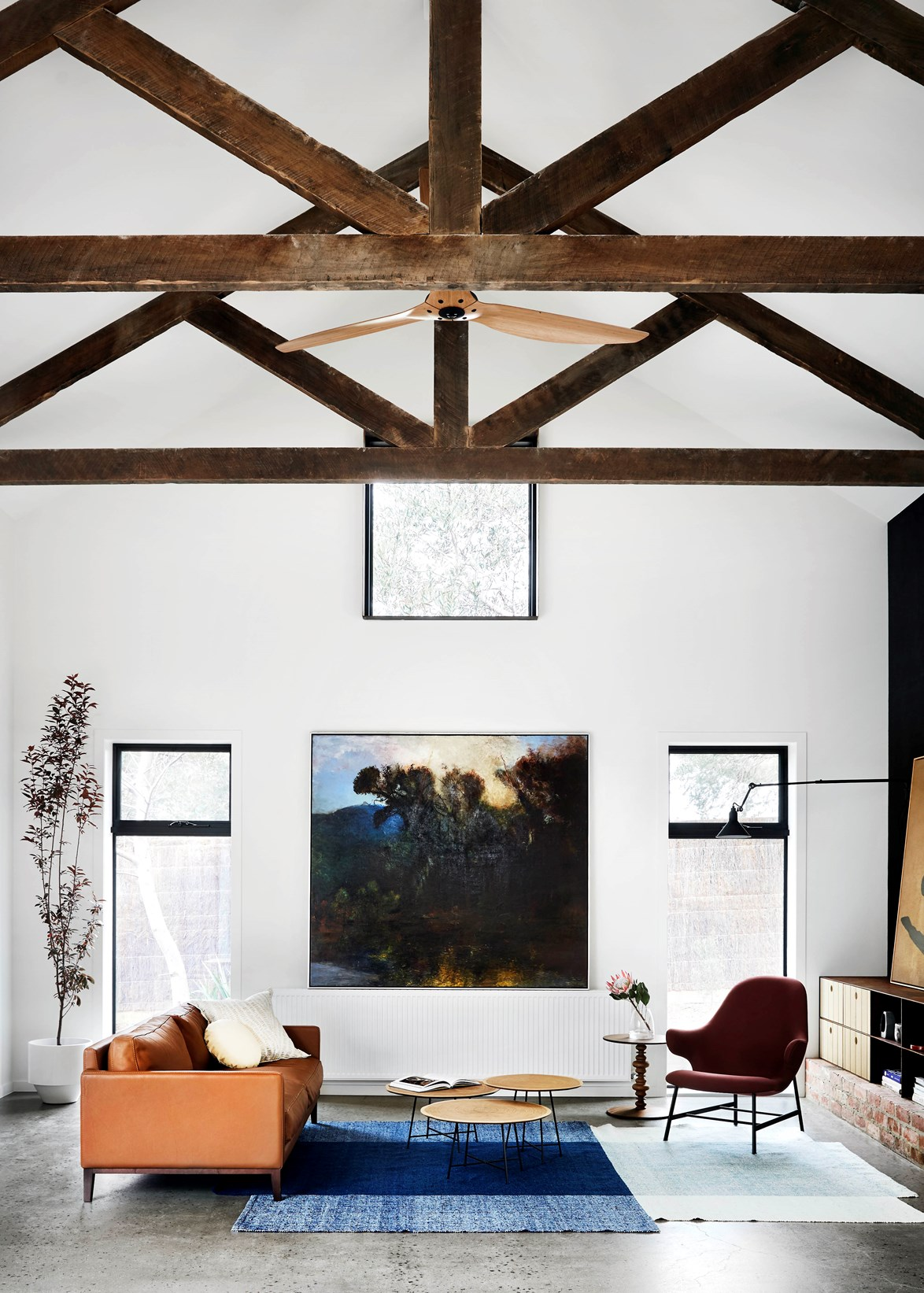 "Designed by Sisalla, Mode Projects and Sabrosa Designs, this [luxe country home](https://www.homestolove.com.au/luxe-country-homes-6774|target=""_blank"") – made up of two distinctly styled 'barns' – feels expansive with exposed reclaimed timber trusses and a recycled brick fireplace. The design brief was to create an interior that reflects the home's beach location while imbuing it with a rustic feel. *Photo: Tess Kelly*"