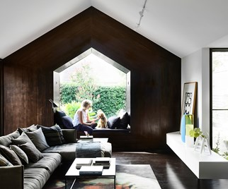Homeowner with dog sitting on the window seat in a living room