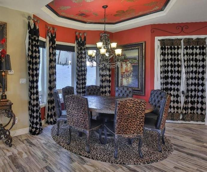 Dining room with red walls, leopard print chairs and checkered curtains.