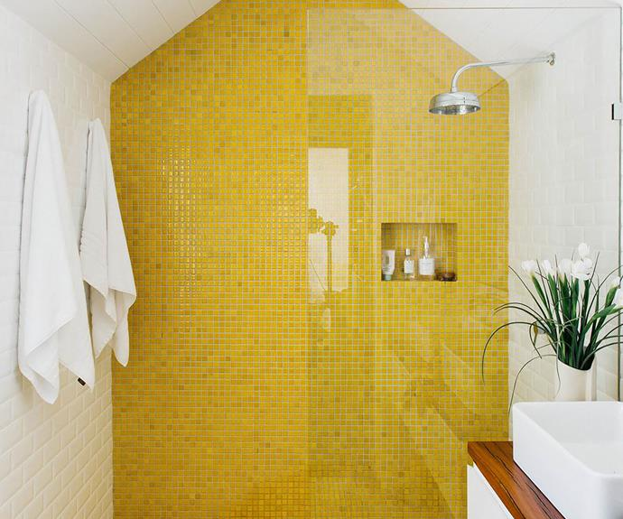 White bathroom with yellow mosaic feature tile wall in the shower.