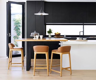 Timber bar stools surround a breakfast bar in a black and white contemporary kitchen