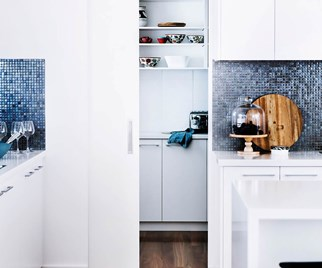 White coastal kitchen with blue mosaic tile splashback