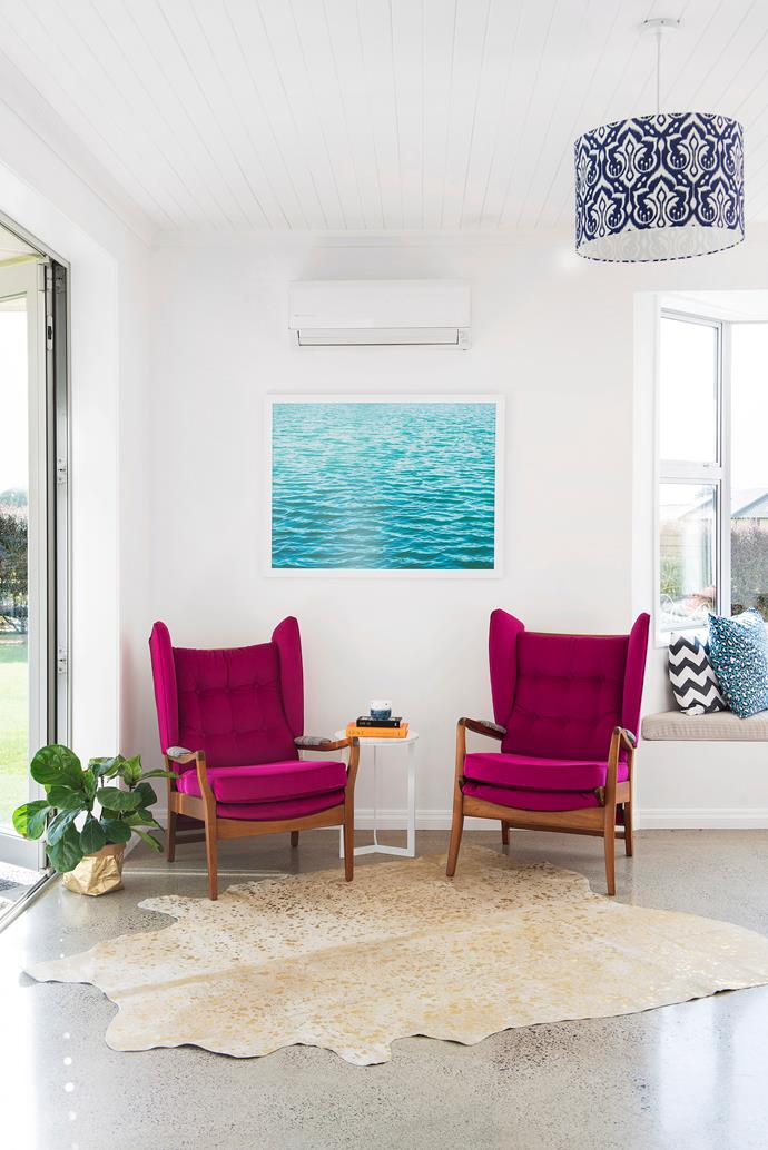 Statement fuscia armchairs turn an otherwise cool space into a cosy and vibrant sitting room. Photo: Helen Bankers /*Your Home & Garden NZ*