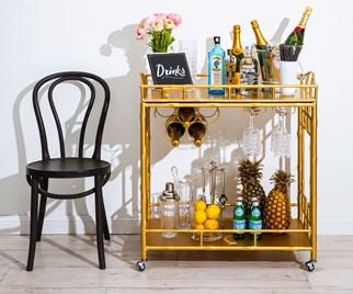 Gold bar cart next to a black chair