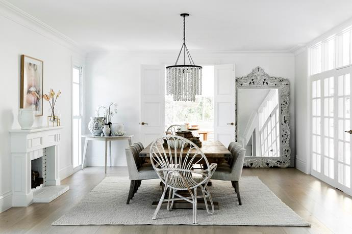 "This room is connected to the formal living room via glass panelled doors. ""I wanted the flexibility to create intimate spaces, so it's lovely to be able to close off this area,"" says Bonnie. The fireplace is from the original house. **Pendant light**, from Deer Willow. **Dining table**, from Oz Design Furniture. 'Lennox' **dining chairs**, from La Maison. 'Jardine' **cane chairs**, from B Seated Global. 'Pia Ivory' **rug**, from Tribe Home. 'Lollipops' **print**, from Nathan+Jac."
