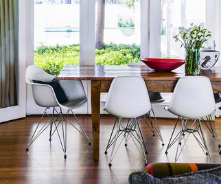 White Eames chairs surrounding a timber dining table