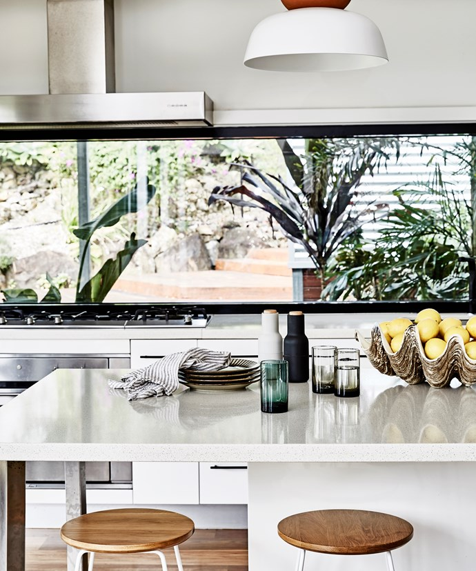 Rather than obstructing the views, a five-metre window doubles as a splashback in the kitchen.