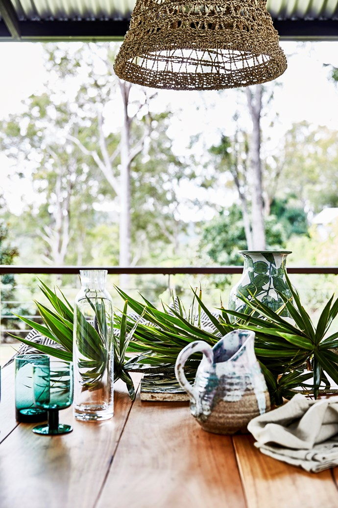The custom-made outdoor dining table displays some of Lauren's treasured pieces, including a tile bought at a Sicilian flea market, carafe by Normann Copenhagen and a vase made by a friend.