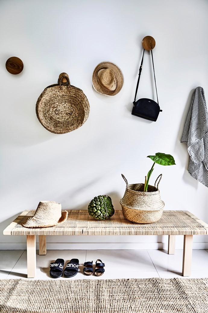 "The [mud room](https://www.homestolove.com.au/mudroom-design-6620|target=""_blank"") near the entry features a rattan Stockholm coffee table from Ikea and African woven baskets from Trader Trove. The walls are painted in Dulux Vivid White"