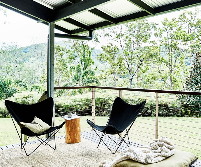 A pair of butterfly chairs on a verandah overlooking bushland