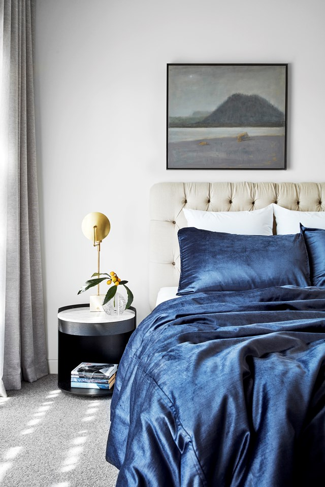 "The master bedroom in this [luxurious homestead built on a horse racing stud](https://www.homestolove.com.au/a-luxurious-homestead-on-a-horse-racing-stud-6816|target=""_blank"") is elegant yet relaxed. Sateen navy bedding screams luxury while a neutral colour palette instils a sense of calm. Photo: Peter Clark / *Belle*"
