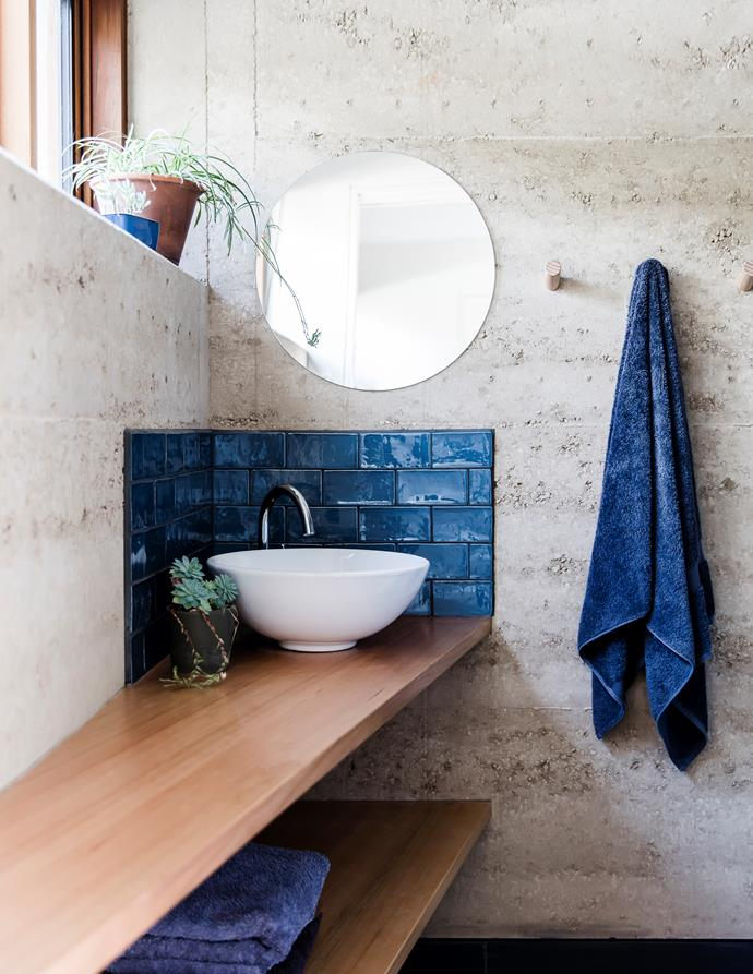 Shiny subway tiles form a striking contrast against the rustic rammed-earth wells in the smaller bathroom, which features a custom-made Tasmanian oak bench.