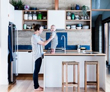 Mother and baby in kitchen of an eco friendly home in Tasmania