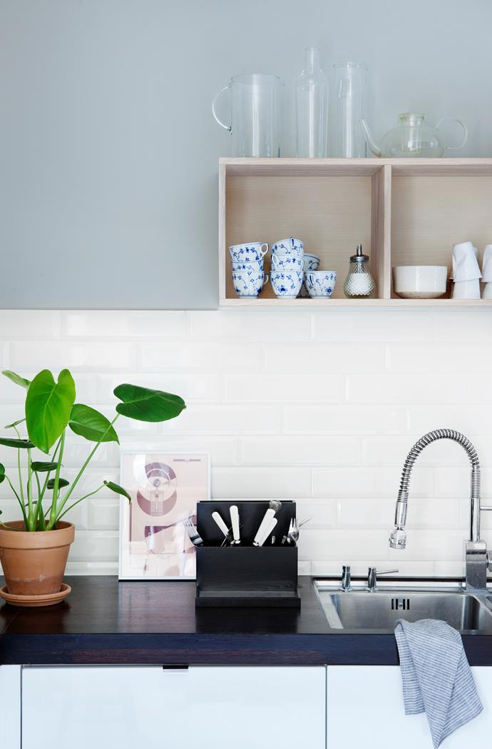 A place for everything and everything in its place, such as these smart display shelves and the chic cutlery container below.